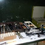 A mixed lot of cutlery and an old radio, one shelf
