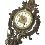 An ornate wall clock with pendulum