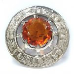 A large white metal Celtic brooch set large amber coloured stone