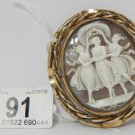A Victorian cameo depicting the three graces with locket back, fashioned with a swivel in yellow metal mount