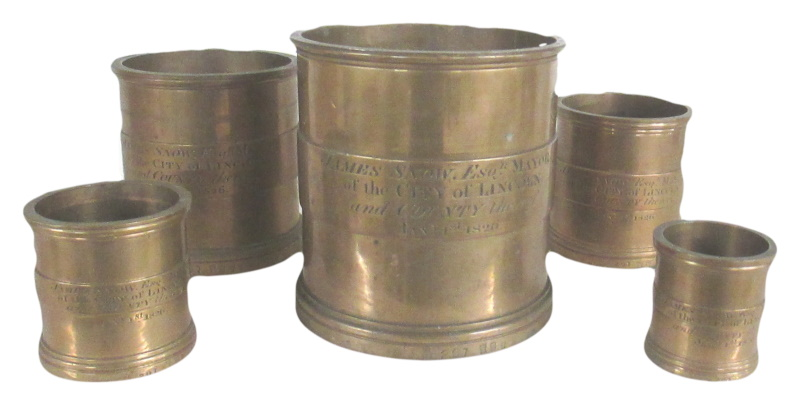 George IV A composite set of five brass graduated measures with lincoln mayor details close up